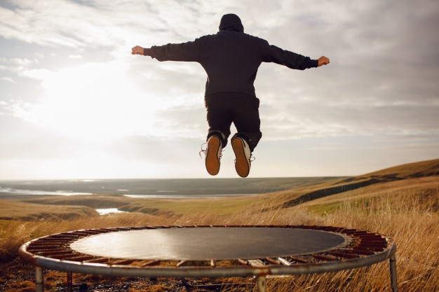 Young man jumping on a trampoline Premium Photo